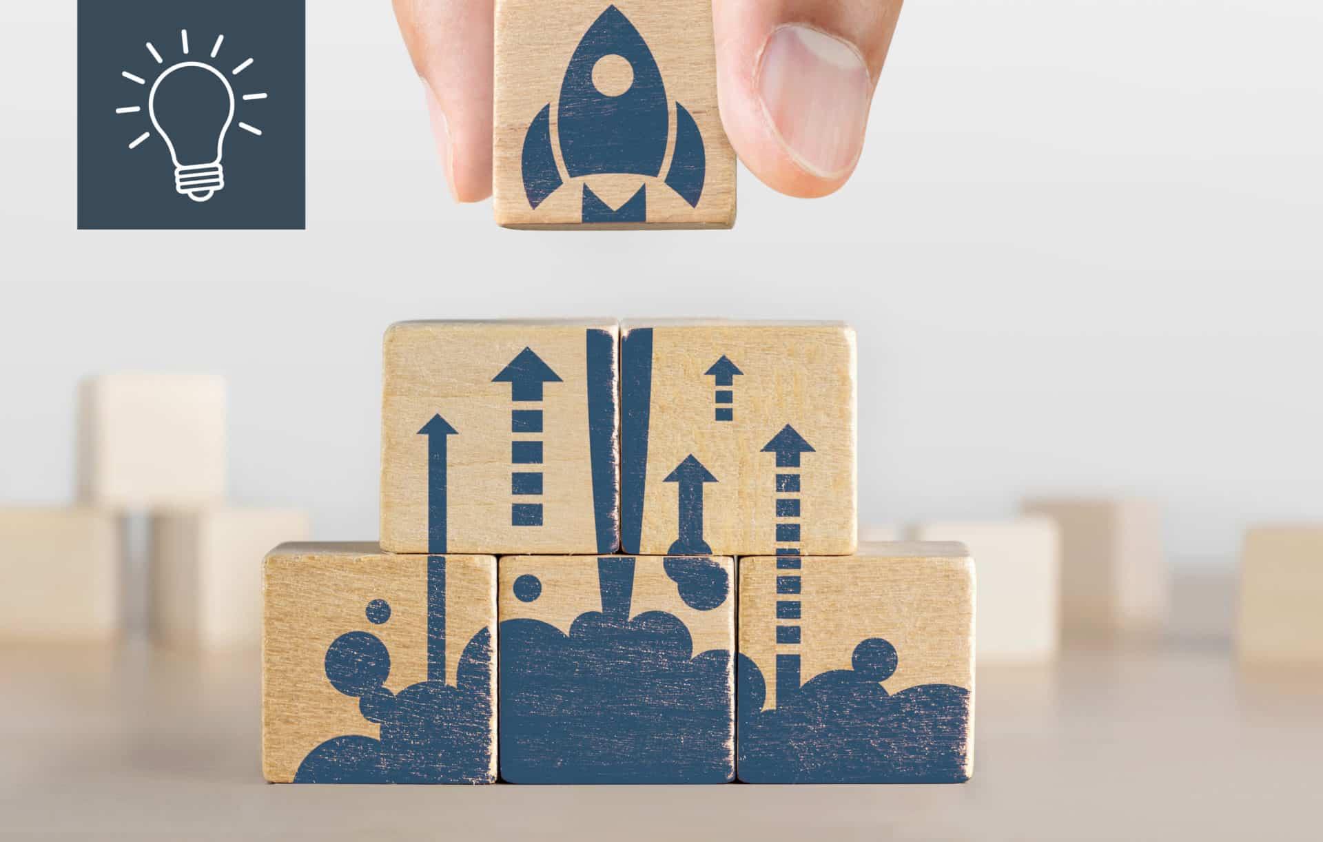 Das Bild zeigt Würfel mit einer Rakete drauf, die für die Überbrückungshilfen III steht. Diese können für Marketingkosten genutzt werden | DESIGNSTUUV Blog